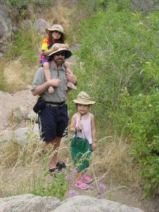 My kids hiking with Daddy while wearing adult ranger-type hats.