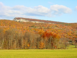 Photo of Skytop cliff in beautiful autumn colors against a green field and blue skies.