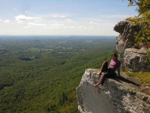 Cliffmama sitting on the edge of the cliff at the top of the Trapps Cliff in the Gunks