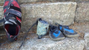 Tiny kids climbing gear: An adult climbing shoe next to a tiny chalk bag and small children's swim shoes.