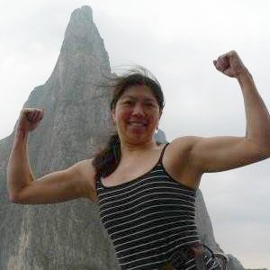 Cliffmama flexing at the top of 7 pitch rock climb Snot Girlz in Potrero Chico, Mexico.