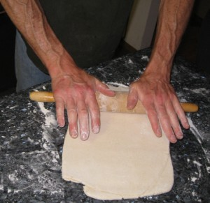 Photo of a man's hands with a rolling pin on dough, making puff pastry.