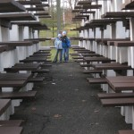 My children standing at the end of a series of stacked up picnic tables in a park off-season.